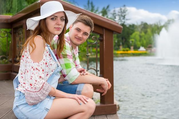 분수와 다른 나무가 배경에 있는 공원의 인공 호수 맞은편 나무 데크에 앉아 있는 커플