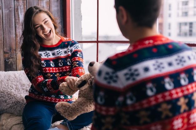 Пара сидит на подоконнике и веселится. девочка держит плюшевого мишку и улыбается.