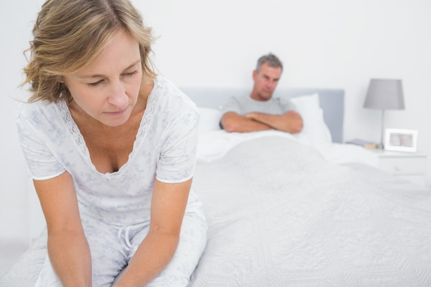 Couple sitting on opposite ends of bed after a fight