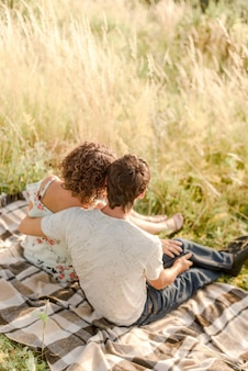 Couple sitting on a plaid in field