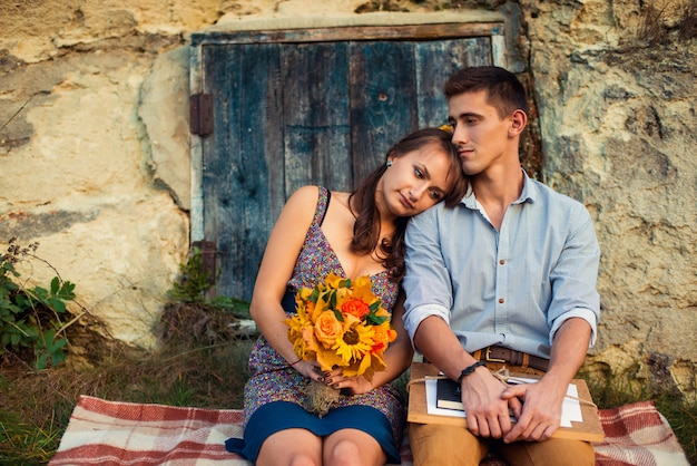 Couple sitting on the plaid near the rock with caves and blue wooden door.