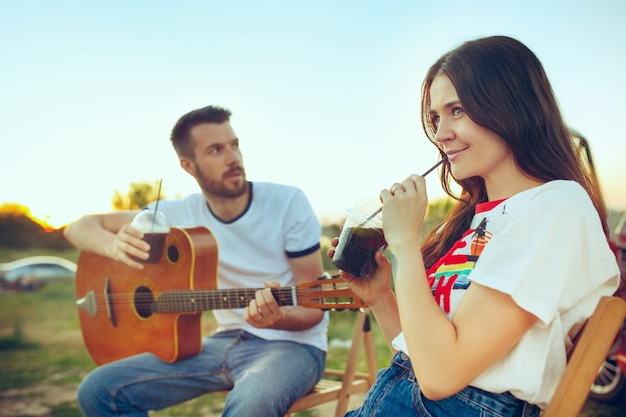 Couple sitting and resting on the beach playing guitar on a summer day near river. love, happy family, vacation, travel, summer concept. caucasian man and woman