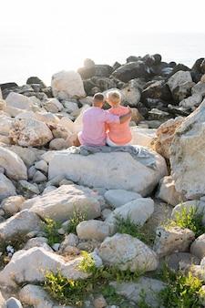 Coppia seduta sulle rocce vista posteriore