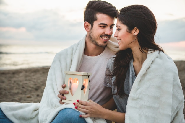 Couple sitting on the sand with a candle and a blanket