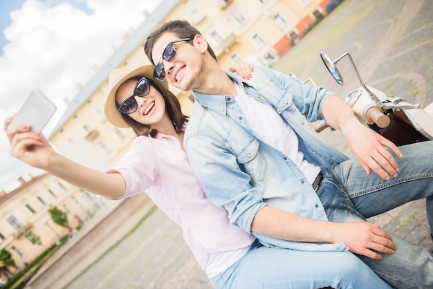 Couple sitting on scooter together and taking selfie.