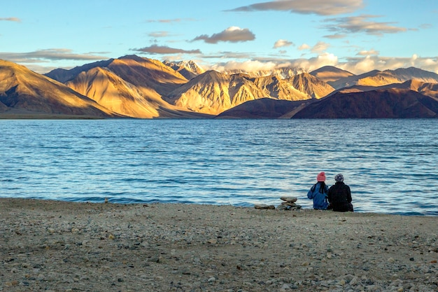 Couple sitting see the sunrise at pangong lake,ladakh,india.