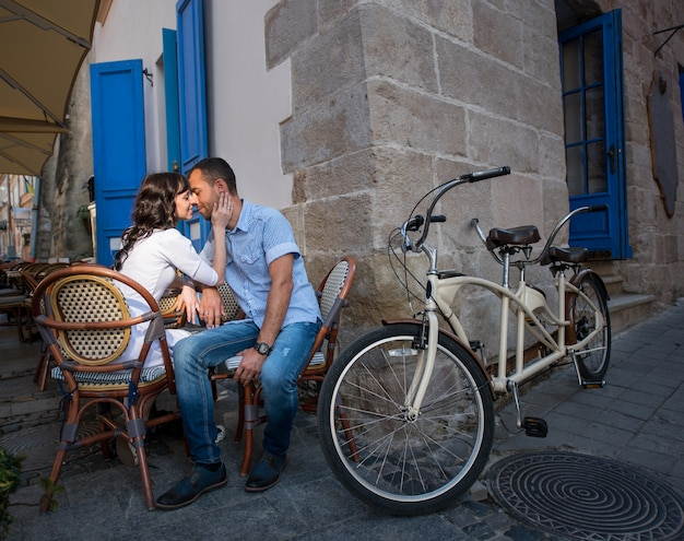 Couple sitting in sidewalk cafe near their tandem bike