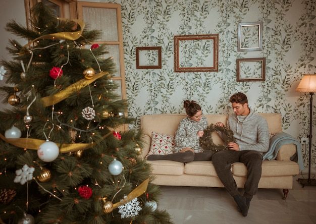 Couple sitting on sofa holding christmas wreath
