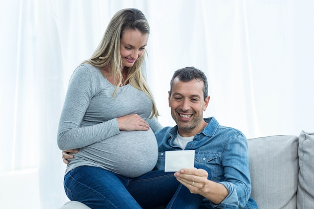 Couple sitting on sofa and looking at ultrasound scan