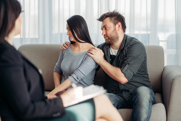 Couple sitting on sofa, psychologist reception