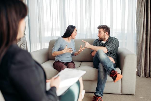 Couple sitting on sofa, psychologist reception