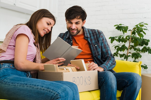 Couple sitting on sofa reading book with box in the living room