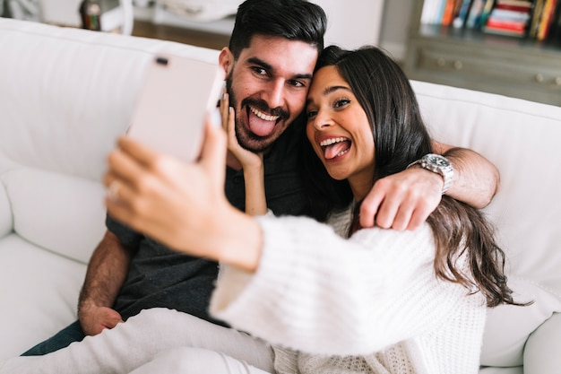 Couple sitting on sofa showing their tongue out taking selfie on smartphone