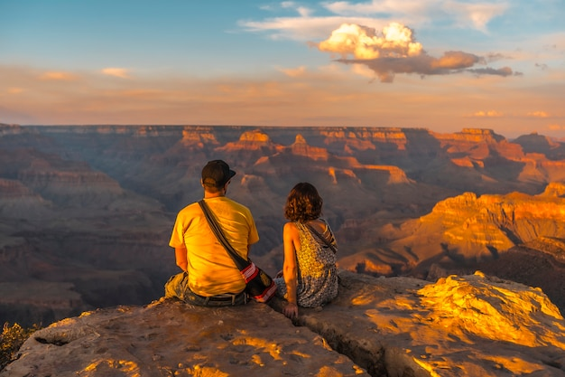A couple sitting at sunset at the powell point of the grand canyon. arizona, vertical photo