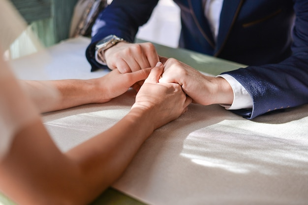 Couple sitting at a table in a cafe and holding hands bride and groom sit at a table and hold hands.