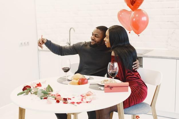 Coppia seduta a tavola, mangiare, parlare e ridere il giorno di san valentino Foto Gratuite