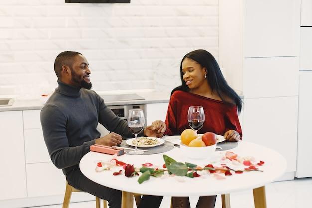 Coppia seduta a tavola, mangiare, parlare e ridere il giorno di san valentino