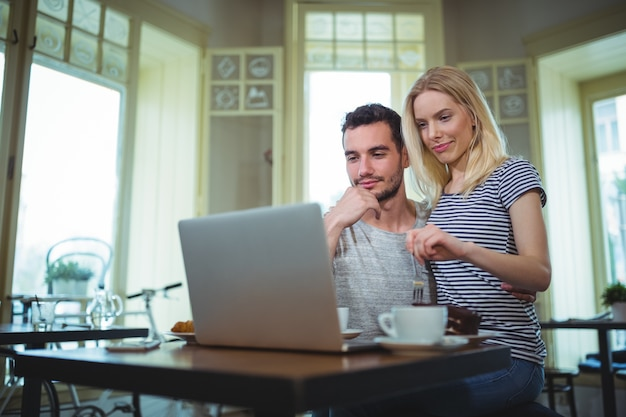 Couple sitting at table and using laptop