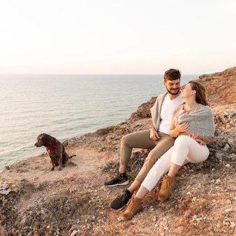 Couple sitting next to their dog on a coast