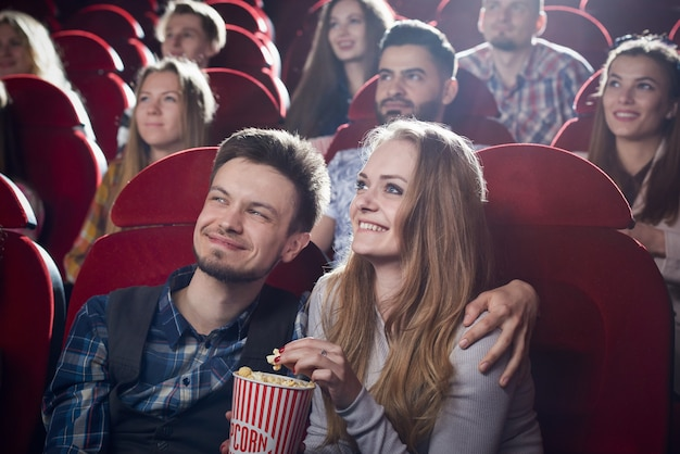 Couple sitting together in cinema, watching comedy or romantic movie. handsome man hugging beautiful girlfriend sitting near while movie review. concept of leisure and free time.