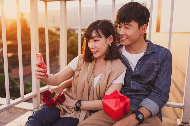 Couple sitting together with a red gift looking at the mobile
