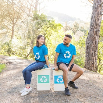 Couple sitting on trash bins in forest