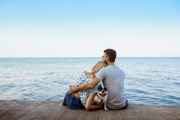Couple sitting with french bulldog near sea