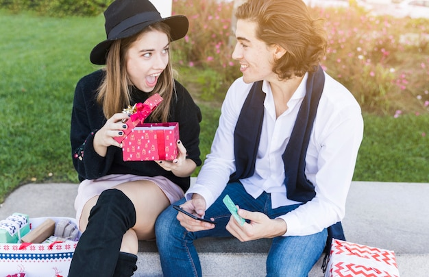Couple sitting with gift box on bench