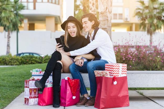 Пара сидит со смартфоном на скамейке