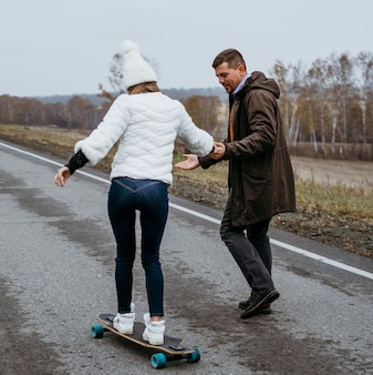 Пара, катающаяся на скейтборде на открытом воздухе вместе на дороге
