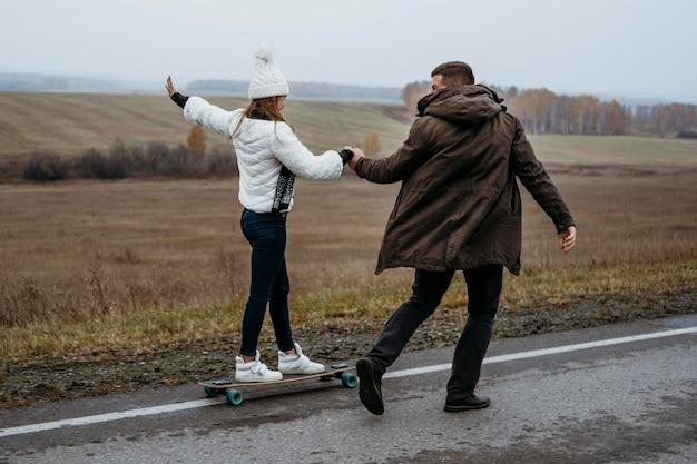 Coppia lo skateboard all'aperto
