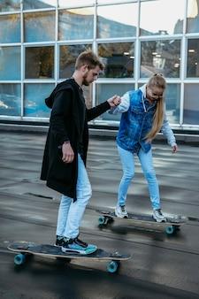 一緒にスケートボードをするカップル