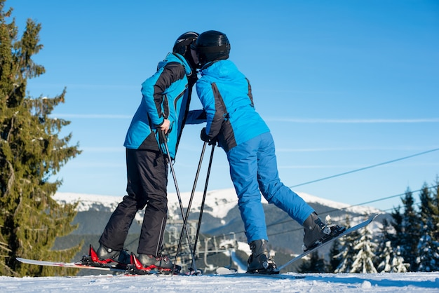 Couple skiers kissing on mountain top with mountain and blue sky in background