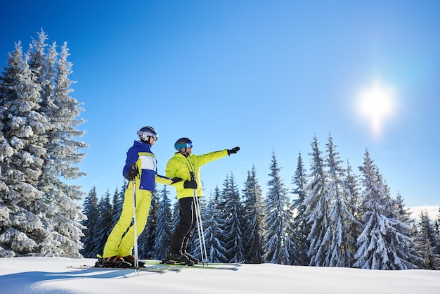 Couple of skiers on skis on hill at ski resort