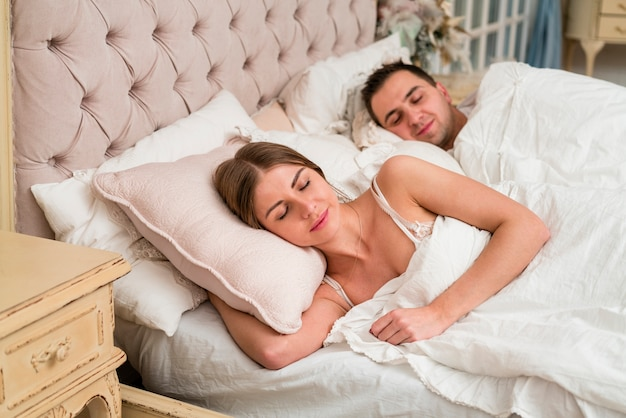 Couple sleeping in bed with duvet