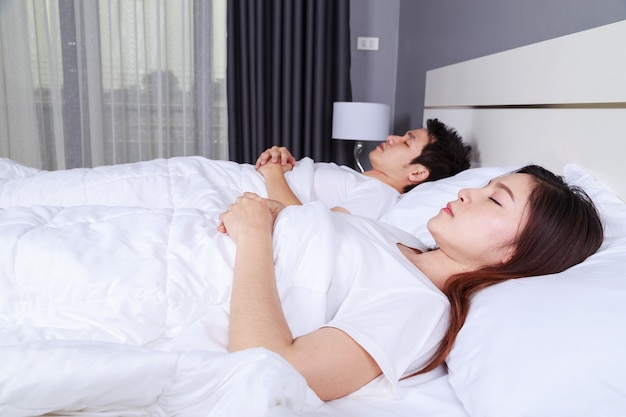 Couple sleeping on a comfortable bed in bedroom at home