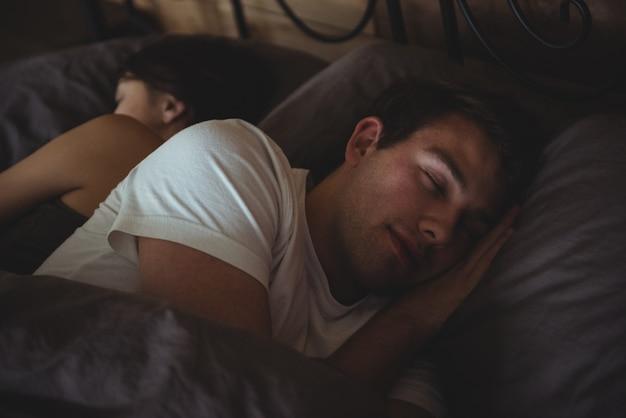 寝室のベッドで寝ているカップル