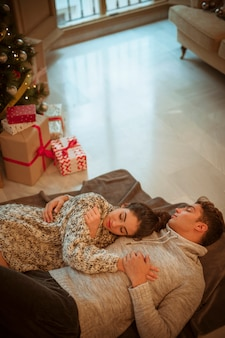 Couple sleeping on floor at presents