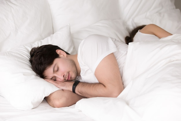 Couple sleeping peacefully together in bed, man wearing smart wr