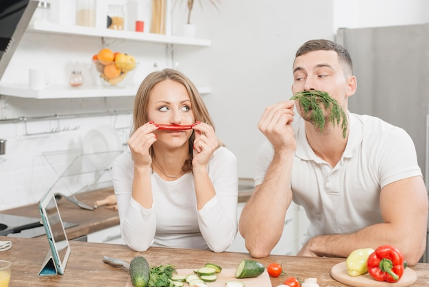 Couple smelling vegetables in kitchen