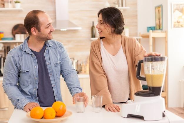믹서기를 사용하여 부엌에서 영양가 있는 과일을 만드는 동안 서로 웃고 있는 커플. 건강하고 평온하고 쾌활한 생활 방식, 다이어트를 먹고 포근하고 화창한 아침에 아침 식사를 준비합니다.
