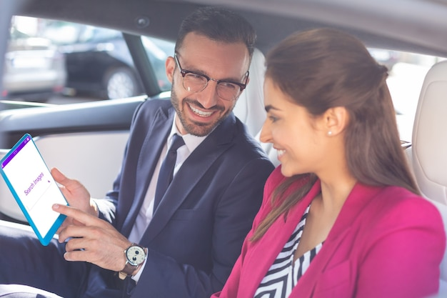 웃는 커플. 차에 앉아 태블릿을 사용하는 동안 웃는 젊은 사업가의 커플