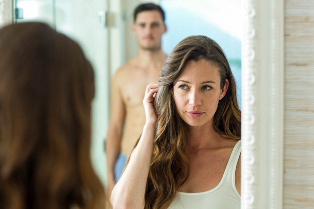 Couple smiling in front of bathroom mirror at home