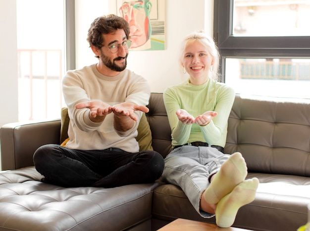 Couple smiling happily with friendly, confident, positive look, offering and showing an object or concept