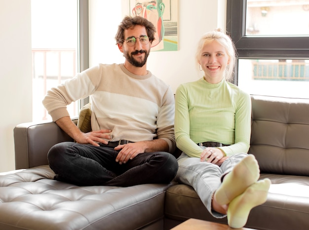 Couple smiling happily with a hand on hip and confident, positive, proud and friendly attitude