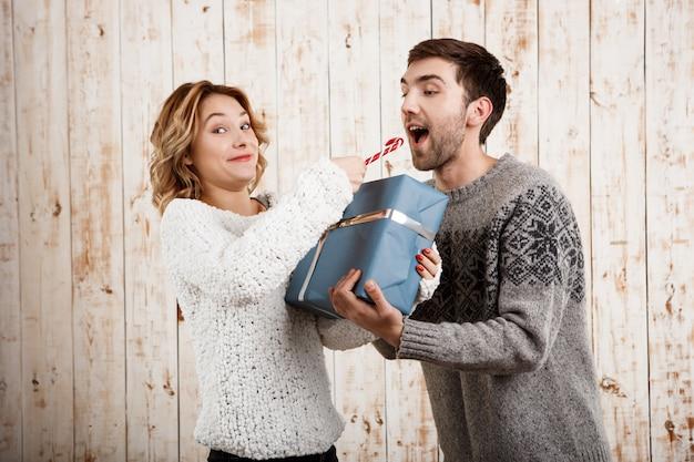 Пары усмехаясь держащ конфету и подарок рождества над деревянной стеной