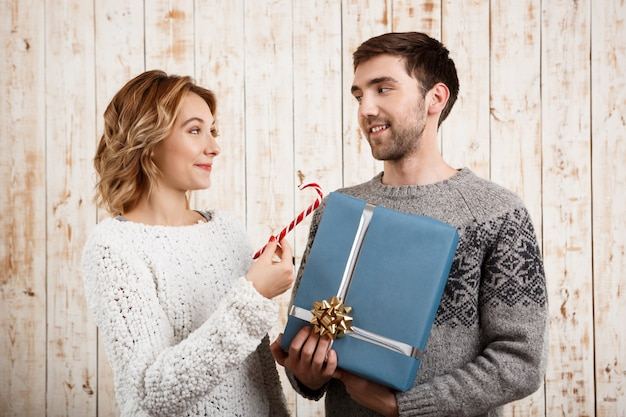 Couple smiling holding christmas candy and gift over wooden wall