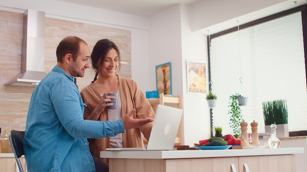 Couple smiling at laptop screen in kitchen. wife holding cup of coffee. husband and wife cooking recipe food. happy healthy together lifestyle. family searching for online meal. health fresh salad