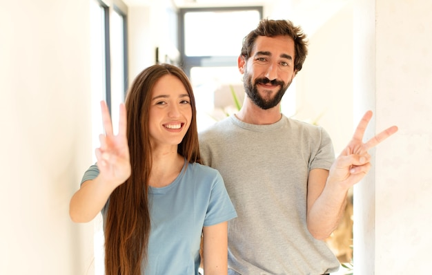 Couple smiling and looking happy, carefree and positive, gesturing victory or peace with one hand