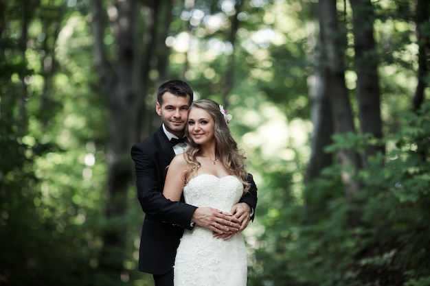 Couple of smiling newlyweds posing outdoors
